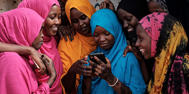 Young Somali women look at a smartphone at Dadaab refugee complex, in northeast Kenya, shakir Essa